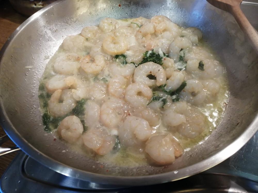 Keď začnú krevety chytať farbu, pridáme nastrúhané dva strúčiky cesnaku a podlejeme 1 dcl bieleho suchého vína.
