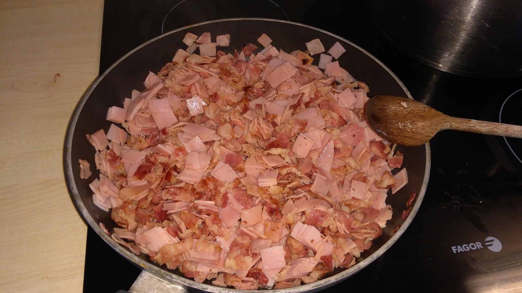 Plátky slaniny a bravčovej šunky nakrájame na jemné prúžky a pridáme na rozpálenú panvicu. Najprv slaninu, aby pustila tuk, potom pridáme šunku.