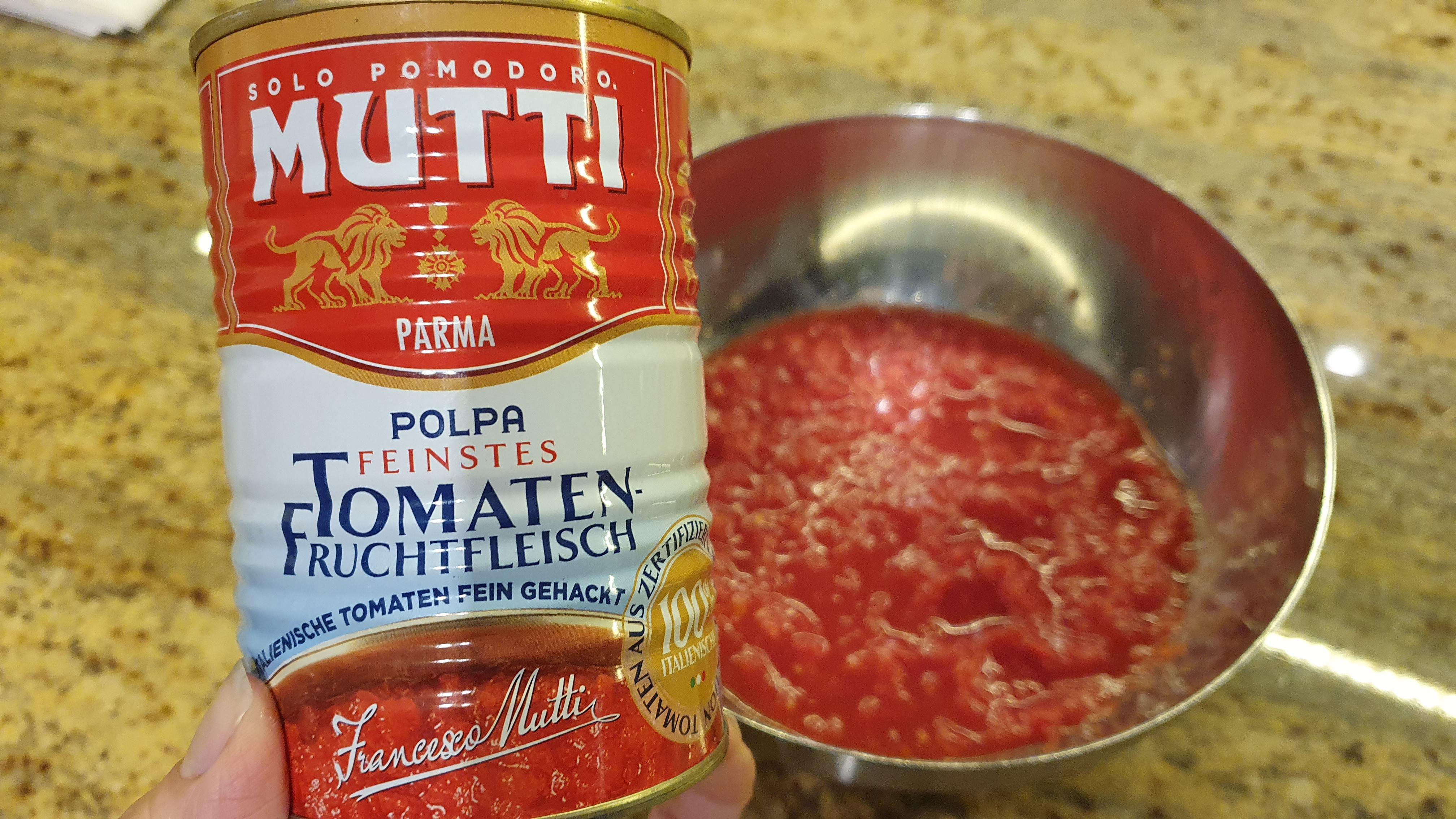 Do misky vylejeme konzervu drvených paradajok. V sezóne môžeme dať aj čerstvé rajčiny bez šupky a pecky v strede, pokrájané na mini kúsky. Osolíme a pridáme zarovnanú lyžicu cukru, pretlačený strúčik cesnaku a oregano.