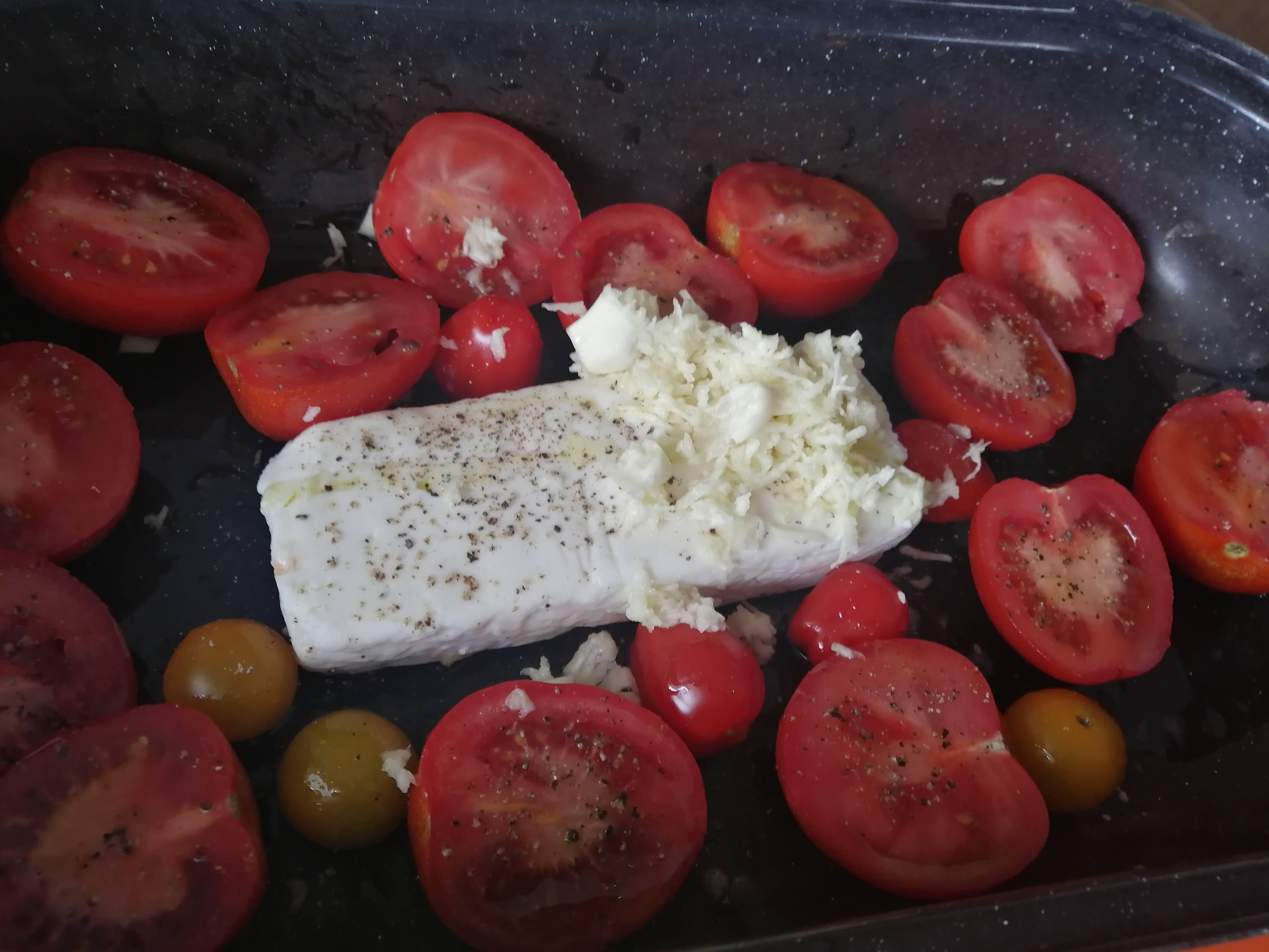 Do plechu vložíme balkánsky syr, cherry paradajky, nakrájané datľové paradajky a nastrúhaný cesnak