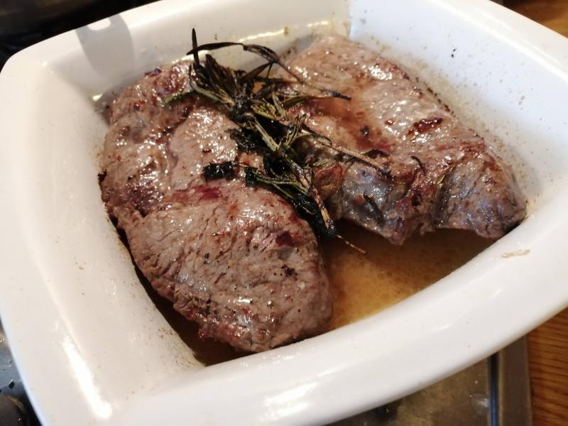 Opražené steaky preložíme z panvice do zapekacej misy a zalejeme rozpusteným maslom s bylinkami z panvice.