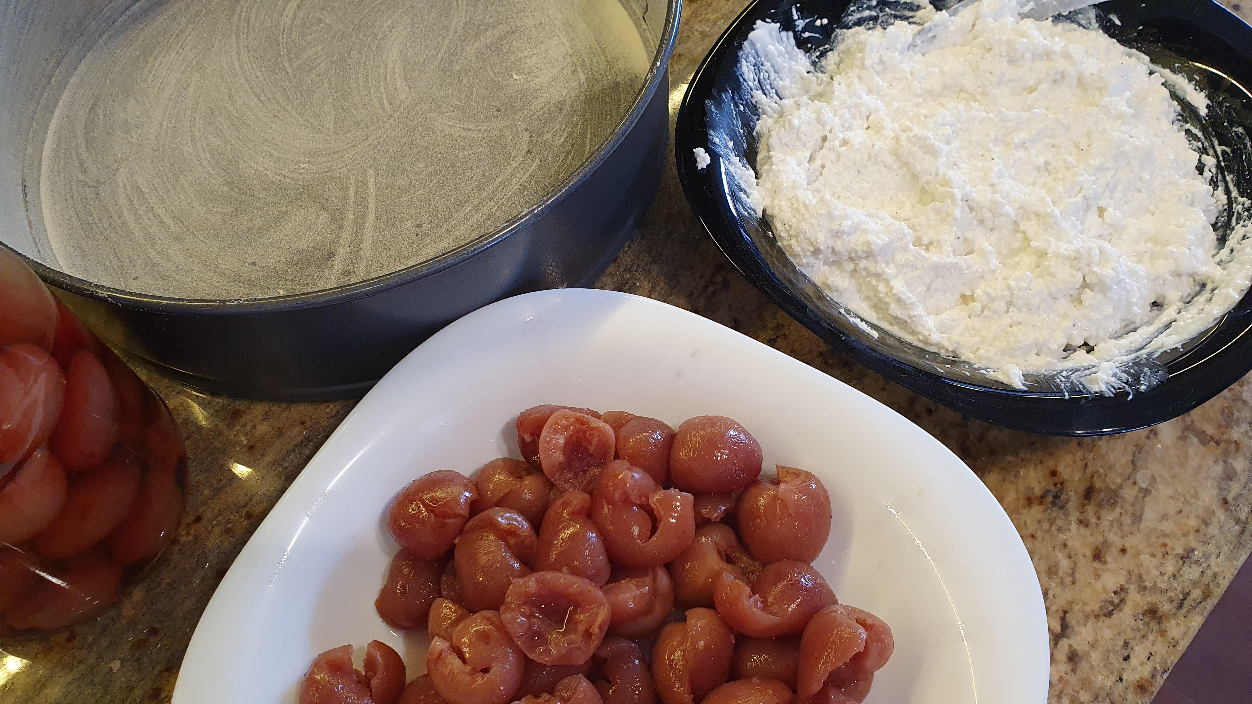 Odkôstkujeme si celý pohár čerešní, vymastíme a múkou vysypeme tortovú formu a vymiešame tvarohovú plnku – 250 g tvarohu, dve lyžice kyslej smotany, lyžica práškového cukru, vanilkový cukor, lyžička citrónovej šťavy a trochu citrónovej kôry.